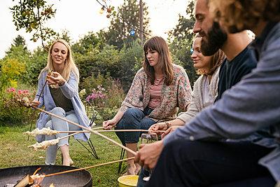 Roasting campfire bread - p788m2037453 by Lisa Krechting