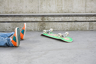 Feet of teenager who has fallen off skateboard - p9246785f by Image Source