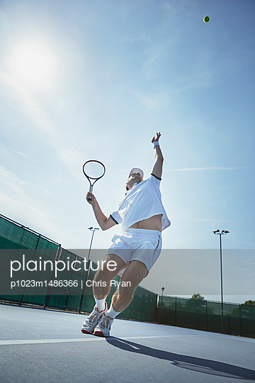 Young male tennis player playing tennis, serving the ball on sunny tennis court