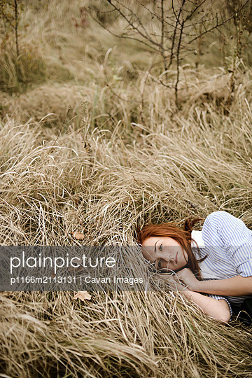 Close-up portrait of teenage girl with red head lying on grassy - p1166m2113131 by Cavan Images
