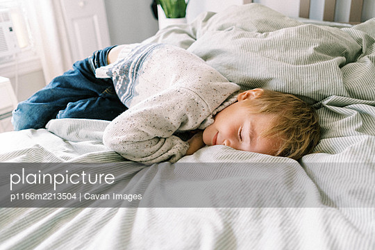 Little boy smushing his face into the soft and cozy blanket on the bed - p1166m2213504 by Cavan Images