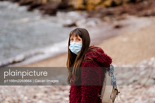 Caucasian young woman on the beach in winter with face mask - p1166m2269664 by Cavan Images