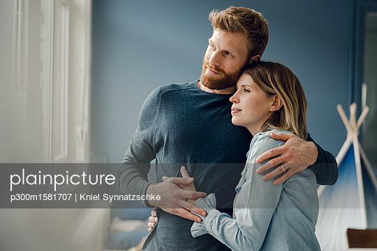 Happy couple embracing at home - p300m1581707 von Kniel Synnatzschke