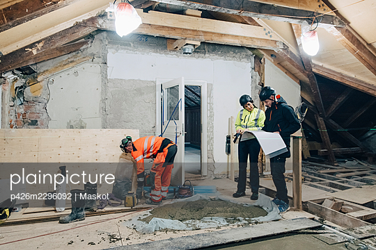 Full length of female building contractor discussing with male worker at site - p426m2296092 by Maskot