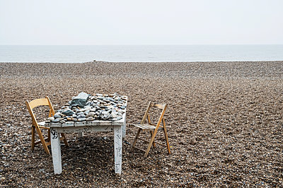 Old rickety white wooden label covered in pebbles and two folding chairs on a shingle beach by the ocean. - p1100m1575758 by Mint Images