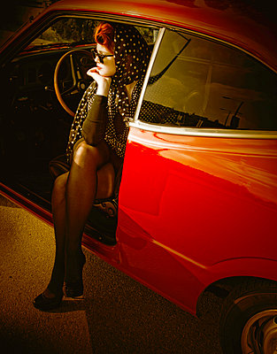 Red-haired woman sits in vintage car - p1445m2125925 by Eugenia Kyriakopoulou