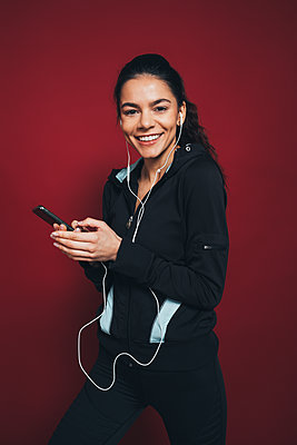 Happy sportswoman with smart phone listening music in front of maroon background - p300m2293739 by alev