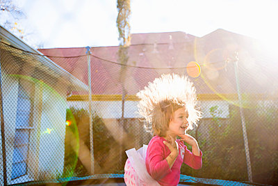 Girl jumping on trampoline in backyard - p429m817378 by Angela Bird
