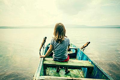 Caucasian girl sitting in boat on still lake - p555m1418673 by Aliyev Alexei Sergeevich