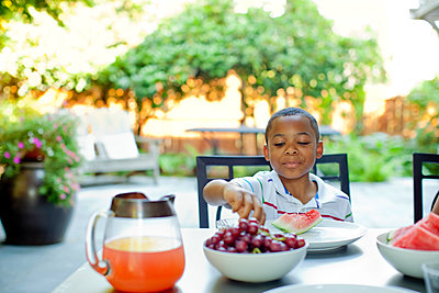 African American boy eating lunch on patio - p555m1478465 by Inti St Clair