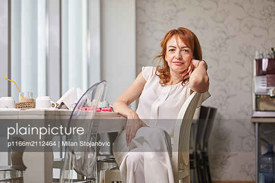Portrait of confident woman sitting on chair in hotel - p1166m2112464 by Milan Stojanovic