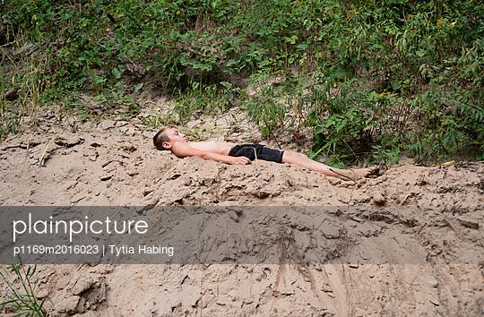 Junge liegt im Sand - p1169m2016023 von Tytia Habing