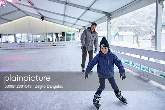 Father and son ice skatng together, having fun on the ice rink - p300m2081549 by Zeljko Dangubic