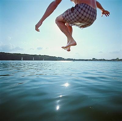 Man Jumping in Lake - p1531m2264214 by Jens Lucking