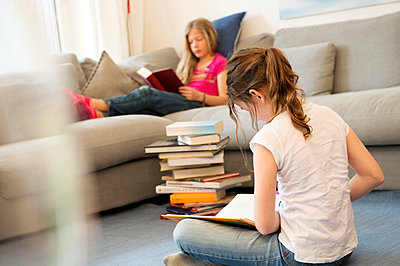 Two girls sitting in the living room reading books - p300m1581699 by Nell Killius
