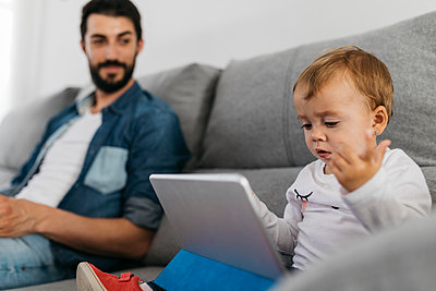 Father sitting on couch while the daughter watching the tablet - p300m1587177 von Josep Rovirosa