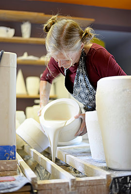Woman pouring liquid into mold in porcelain workshop - p300m2004695 by Bernd Friedel