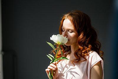 Portrait of redheaded woman smelling white peony - p300m2140291 by Kniel Synnatzschke
