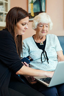 Grandmother and granddaughter using laptop at home - p426m1017793f by Maskot