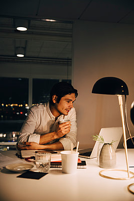 Male entrepreneur working late while using laptop sitting with coffee cup at desk in office - p426m2194745 by Maskot