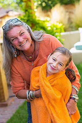 Caucasian grandmother wrapping granddaughter in towel in backyard - p555m1420850 by Marc Romanelli