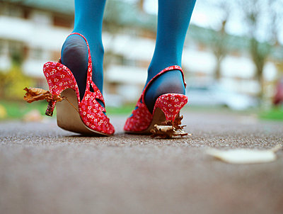 Woman with leaves stuck to her shoes - p92410852f by Image Source