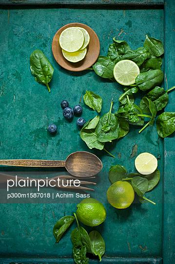 Salad ingredients and salad cutlery on green ground - p300m1587018 von Achim Sass