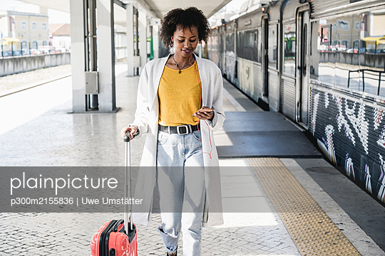 Smiling young woman with earphones and smartphone at platform - p300m2155836 by Uwe Umstätter