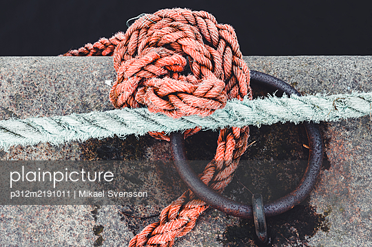 Sailor knots on jetty tied in round metal ring - p312m2191011 by Mikael Svensson