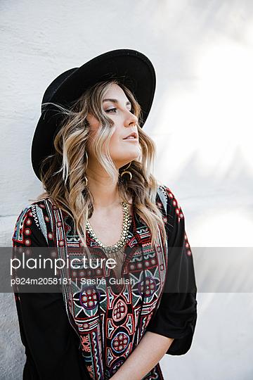 Fashionable woman posing against white wall - p924m2058181 by Sasha Gulish