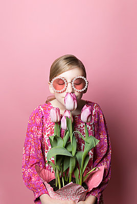 Blonde tween girl in sunglasses smells pink tulips on pink background - p1166m2171546 by Cavan Images