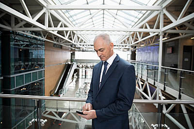 Businessman using smart phone on office atrium balcony - p1192m2093717 by Hero Images
