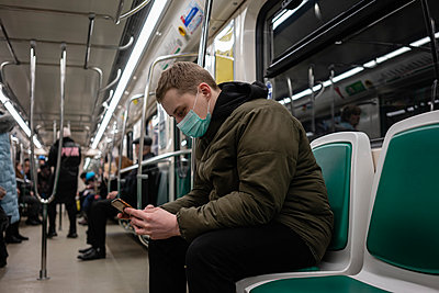 Young man in commuter train, wearing face mask, using smartphone - p300m2170810 by Vasily Pindyurin