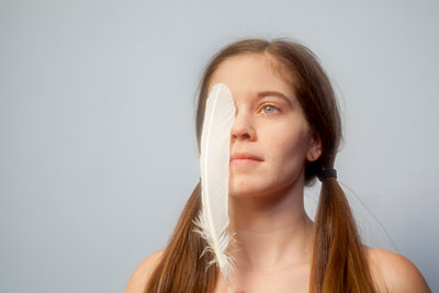 Young woman holding a white feather over her eyes - p397m1120379 by Peter Glass