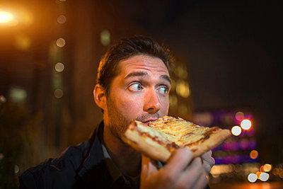 Man eating pizza on city street - p924m768446f by Steve Prezant