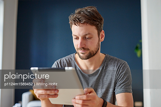 Junger Mann mit Tablet Computer - p1124m1589452 von Willing-Holtz