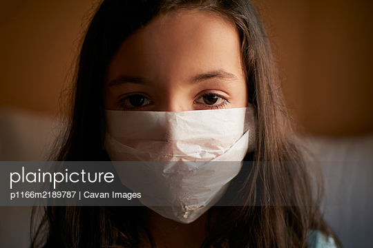 Girl with face mask in quarantine at home for covid-19 coronavirus - p1166m2189787 by Cavan Images