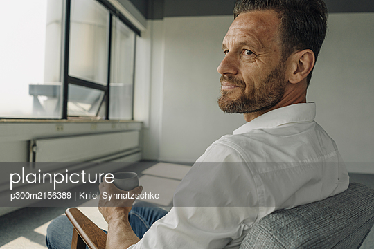 Mature businessman with cup of coffee sitting in armchair in empty office - p300m2156389 by Kniel Synnatzschke