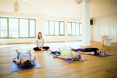 Women practicing yoga in class - p1026m1139950 by Patrick Frost