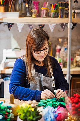 Woman working at a table in a craft workshop, making a paper flower wreath. - p1100m1544333 by Mint Images