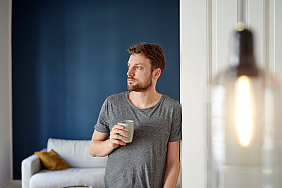 Young man has a cup of coffee at home - p1124m1589454 by Willing-Holtz