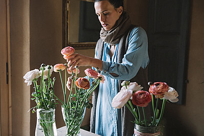 Woman arranging fresh flowers - p300m2004654 von Alberto Bogo