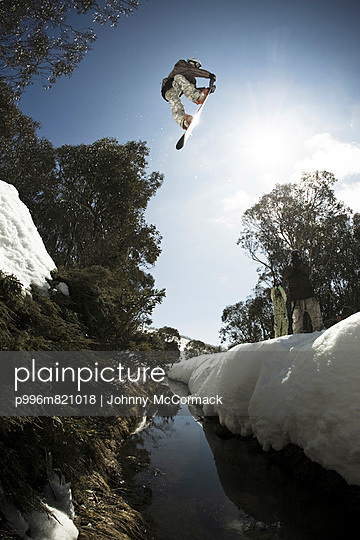 Snowboarder jumps across a tree lined river