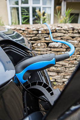 An elctric car and charging point, parked on the side of the road outsiude a house with blue cable. - p1057m1463581 by Stephen Shepherd