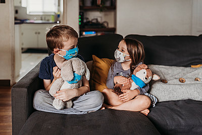 Preschool age girl and school age boy with masks sitting on couch - p1166m2207779 by Cavan Images
