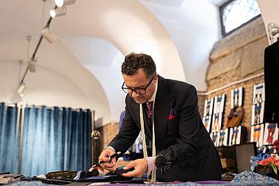 Senior dressmaker pinning chosen fabric - p1166m2261415 by Cavan Images