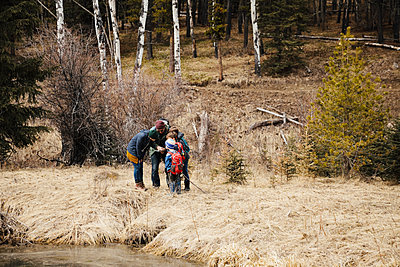 Family hiking, looking at map in woods - p1192m2094162 by Hero Images