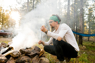 Man with marshmallow crouching at campfire, Wasatch Cache National Forest - p1427m2213552 by Jessica Peterson