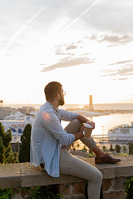 Man sitting on a wall on lookout above the city with view to the port, Barcelona, Spain - p300m2154493 by VITTA GALLERY