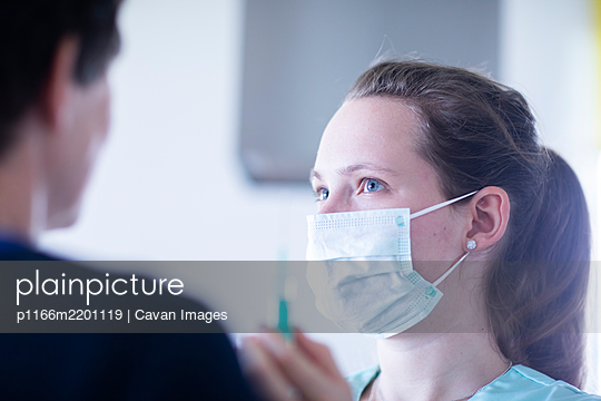 nurse and a patient with mouthpiece and syringe - p1166m2201119 by Cavan Images